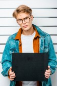 handsome hipster holding empty prison board while standing in front of police line up