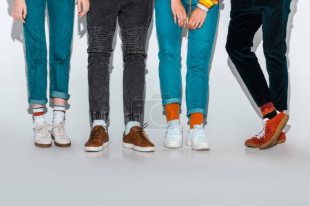low section view of stylish hipsters legs on grey