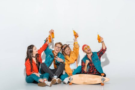Photo for Cheerful stylish hipsters sitting with skateboard and holding beer bottles - Royalty Free Image
