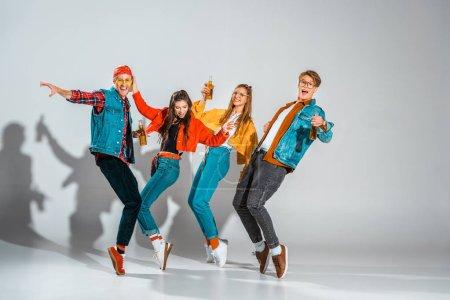 Photo pour Joyeux hipsters élégants avec des bouteilles de bière dansant sur gris - image libre de droit