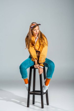 beautiful stylish girl posing on stool on grey