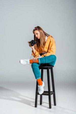 Foto de Chica elegante mirando a cámara de fotos mientras estaba sentado en el taburete en gris - Imagen libre de derechos