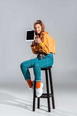 schönes Mädchen zeigt Daumen hoch und Tablet mit leerem Bildschirm auf grau