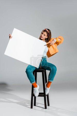 Photo pour Belle fille élégante pointant sur une pancarte blanche sur fond gris - image libre de droit