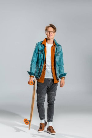 young hipster in denim jacket posing with skateboard on grey