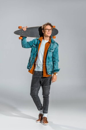 Photo for Young male skateboarder in denim jacket posing with longboard on grey - Royalty Free Image