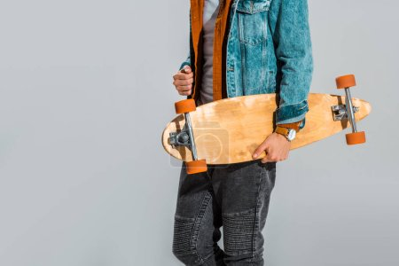 cropped view of stylish skateboarder holding longboard isolated on grey