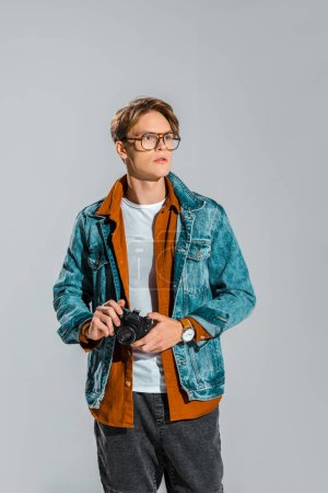Photo pour Jeune photographe beau tenant appareil isolé sur fond gris - image libre de droit