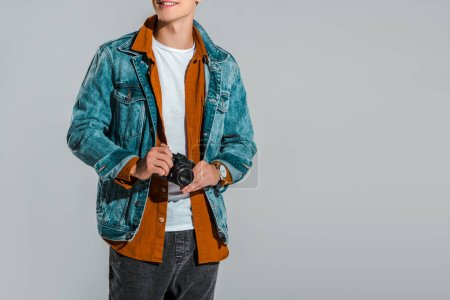 Photo for Cropped view of young stylish tourist holding photo camera isolated on grey - Royalty Free Image