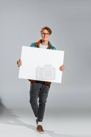 happy handsome hipster holding empty board on grey