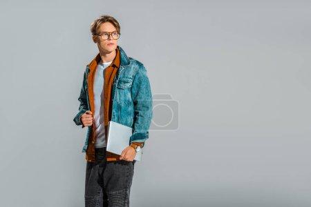 Photo pour Beau style hipster mâle posant avec ordinateur portable isolé sur fond gris - image libre de droit