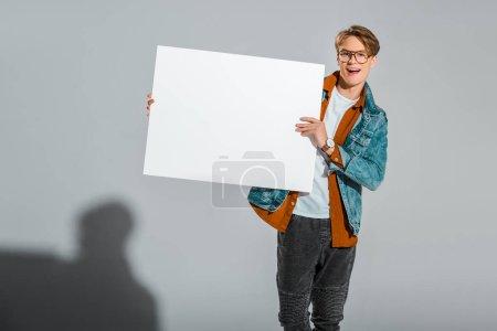 Photo pour Hipster mâle excité, tenant une pancarte vide sur fond gris - image libre de droit