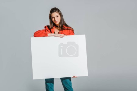 beautiful girl holding blank placard isolated on grey