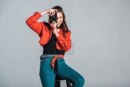 Photo pour Fille souriante prenant des photos sur la caméra isolé sur gris - image libre de droit