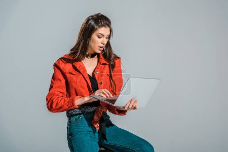 shocked young woman using laptop isolated on grey