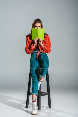 attractive stylish student holding green book while sitting on stool on grey