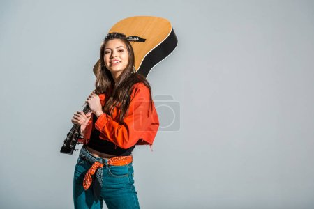 Photo for Beautiful cheerful girl posing with acoustic guitar isolated on grey - Royalty Free Image