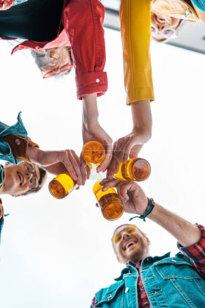bottom view of young friends clinking with beer bottles together
