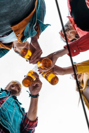 bottom view of happy friends clinking with beer bottles together