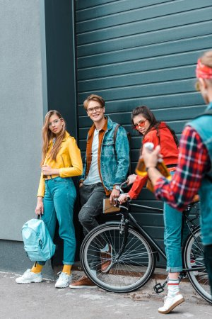stylish male hipster brought beer for young smiling friends on street with bike