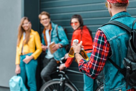 stylish hipster brought beer for young friends on street with bike