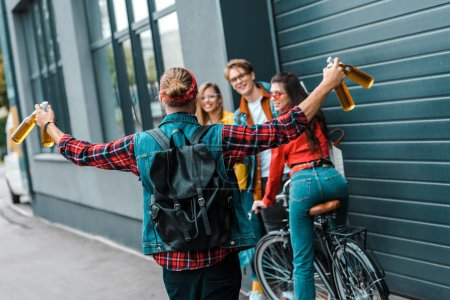 Photo for Excited male hipster brought beer to happy friends on street with bicycle - Royalty Free Image