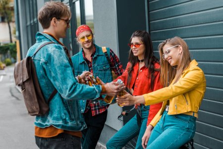 cheerful friends holding beer from bottles on street