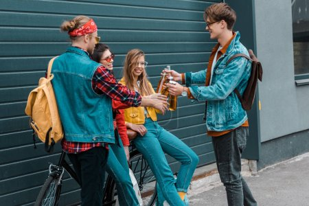 hipsters with bicycle clinking with beer bottles together on street