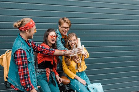 cheerful friends clinking with beer bottles on street