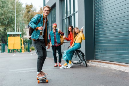 young hipsters with longboard and bike having fun on street