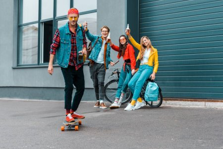 happy young friends with skateboard and bicycle having fun on street