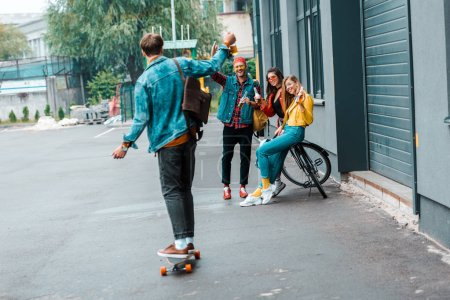 happy hipsters with skateboard and bicycle on street