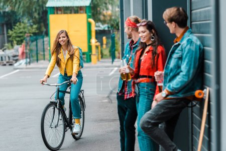attractive stylish girl riding bike near friends with beer bottles on street