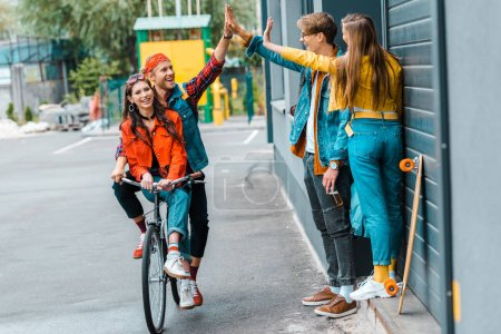 stylish couple riding bicycle and giving highfive to friends on street