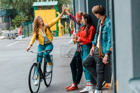 happy stylish girl riding bike and giving highfive to friends on street