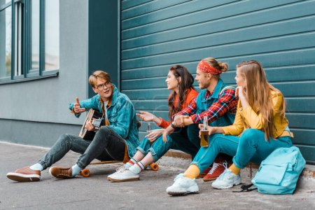 hipsters drinking beer together on street while man playing acoustic guitar