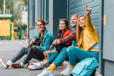 Photo for Young friends spending time together on street while man playing guitar and woman pointing somewhere - Royalty Free Image