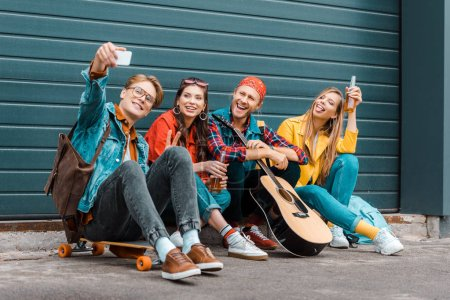 Photo for Young friends with beer, skateboard and guitar taking selfie on smartphone - Royalty Free Image