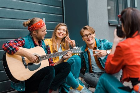 girl taking photo of hipsters with acoustic guitar on street