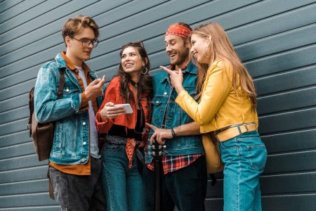 happy young hipsters using smartphone together on street