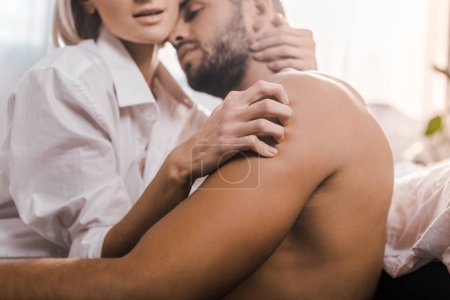 cropped shot of passionate young woman scratching back of shirtless boyfriend