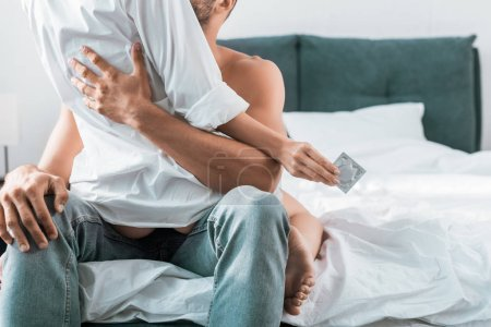 cropped shot of passionate couple with condom sitting on bed