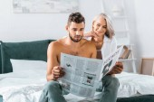 beautiful young couple reading newspaper together in bedroom