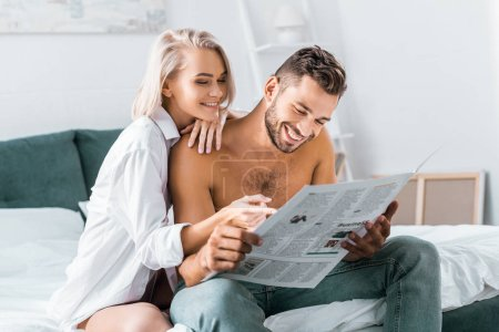 happy young couple reading newspaper together in bedroom