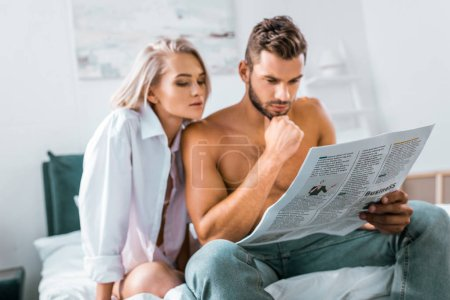 attractive young couple reading newspaper together in bedroom