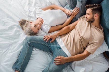 Photo pour Vue aérienne de beau jeune couple se relaxant ensemble dans la chambre - image libre de droit