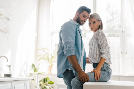 side view of passionate young couple hugging in kitchen, girlfriend looking at camera