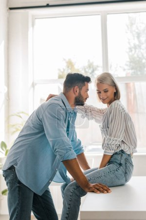 side view of smiling young couple hugging in kitchen while girlfriend sitting on kitchen counter