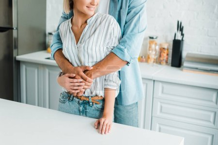 Photo for Cropped image of boyfriend hugging smiling girlfriend from back in kitchen - Royalty Free Image