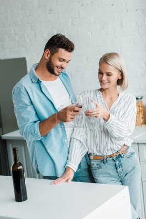 smiling young couple clinking with glasses of red wine in kitchen